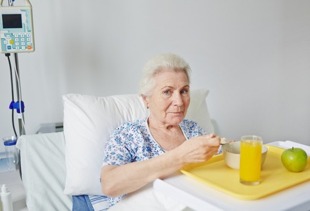 hospital patient: Patient eating breakfast in hospital bed