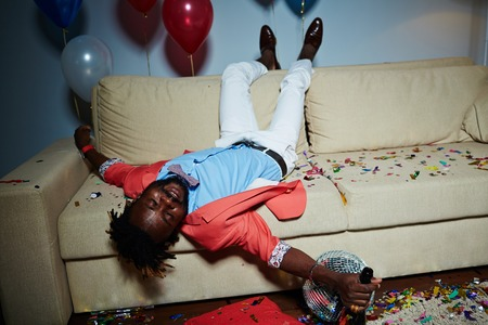 messy room: Drunk guy with bottle of champagne lying on sofa in messy room after party
