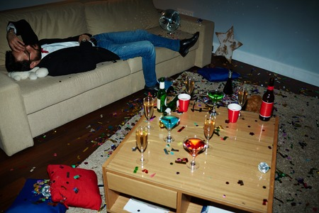 tiresome: Exhausted man lying on sofa after tiresome party