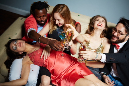 clubber: Flutes with champagne in hands of ecstatic friends during toast Stock Photo