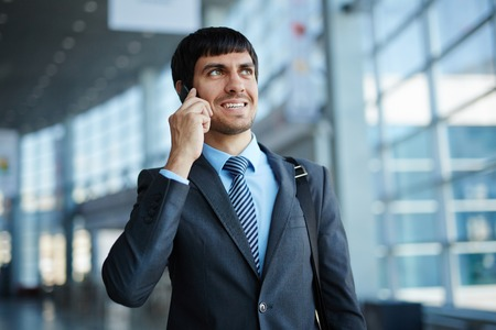 somebody: Handsome employee with cellphone consulting somebody
