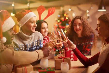 holiday gathering: Cheerful teens toasting with champagne on Christmas evening