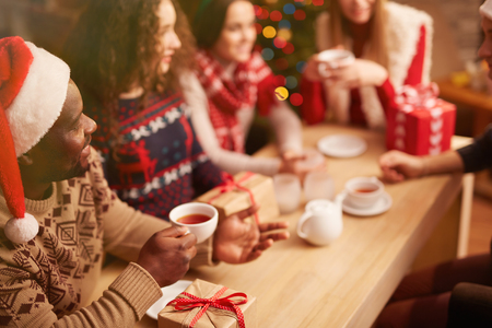 holiday gathering: Guy in Santa cap with cup of tea talking to his friends during xmas party Stock Photo