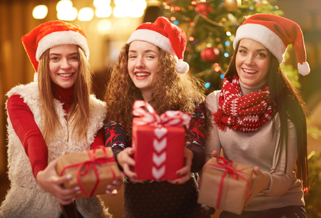 happy christmas: Three happy girls in Santa caps showing packed gifts