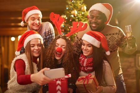 grupo de hombres: amigos de éxtasis en traje de Navidad que hacen autofoto durante la fiesta en casa Foto de archivo