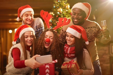party night: Ecstatic friends in xmas attire making selfie during home party