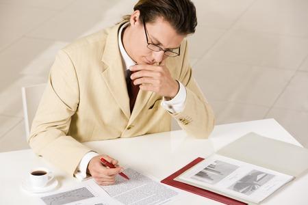 Image of thinking businessman reading the document photo