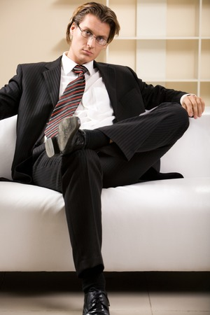 Portrait of confident businessman sitting on the sofa crossing his legs photo