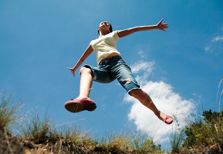 angle: Image of girl in casual clothing jumping in the park