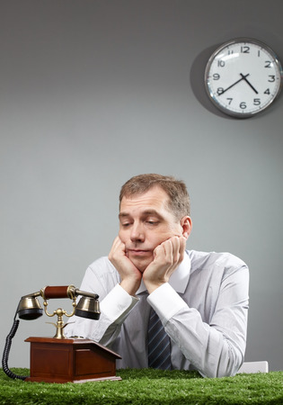 businessman waiting call: Portrait of businessman looking at telephone and expecting call