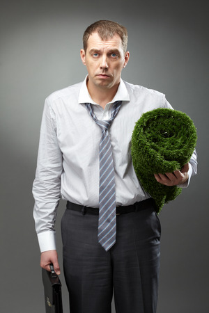 personas tristes: Tired manager holding briefcase and artificial grass Foto de archivo