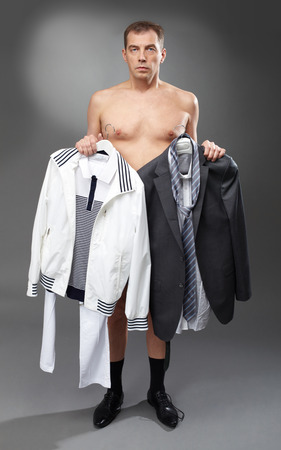 formal dressing: Portrait of pensive bachelor holding sports clothing and suit Stock Photo