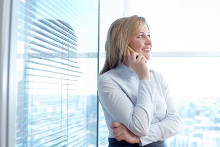 ejecutivo en oficina: Un secretario llamando por teléfono móvil en la habitación