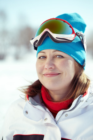 Portrait of woman in ski suit looking at camera photo