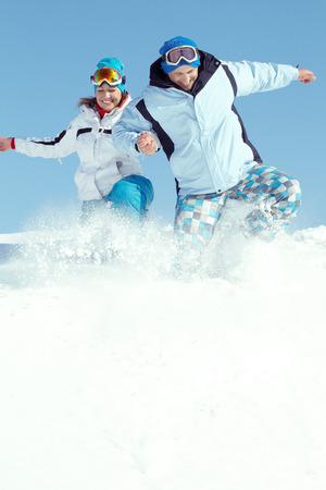 Cheerful couple in ski suit jumping in snow photo