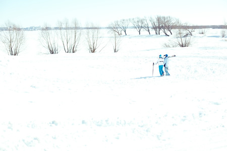 Two skiers walking in desert winter field photo