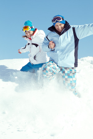 Cheerful couple in ski suit going down snowy hill photo