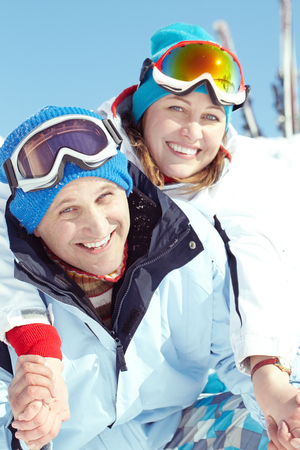 Portrait of married couple in ski suit embracing and looking at camera photo