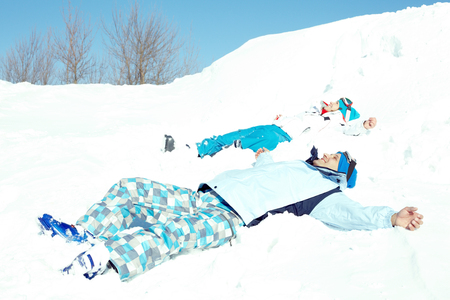 Couple lying on snow and enjoying good winter day photo