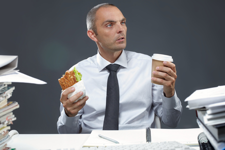 working desk: Portrait of manager with sandwich and coffee at his workplace