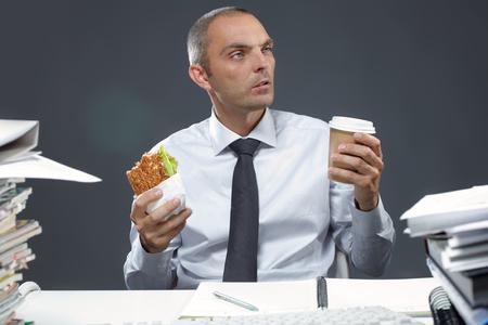 hombre comiendo: Retrato del encargado con el emparedado y el café en su lugar de trabajo