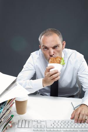 negocios comida: Administrador de mascar sándwich mientras se trabaja