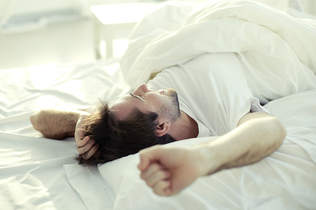 Man luxuriating in bed in the morning