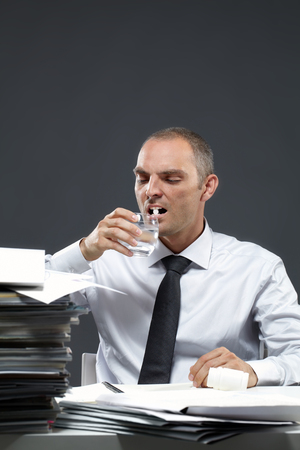 businessman in office: Manager taking medicine at workplace