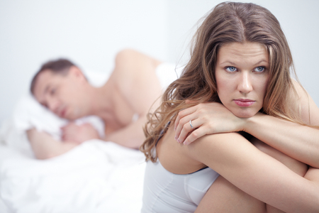 impotence: Dissatisfied woman sitting by bed where her husband is sleeping