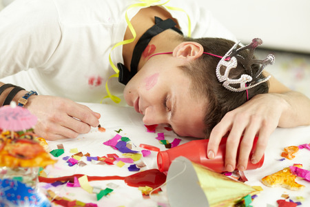rowdy: Young man in party hat sleeping on table among confetti and remnants of food