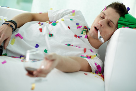 Young man sleeping on sofa in party hat all in confetti and with a wine glass