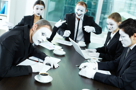 buisness woman: Business team of mimes sitting in board room and communicating Stock Photo