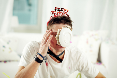 rowdy: Young man with cake on his face at birthday Stock Photo