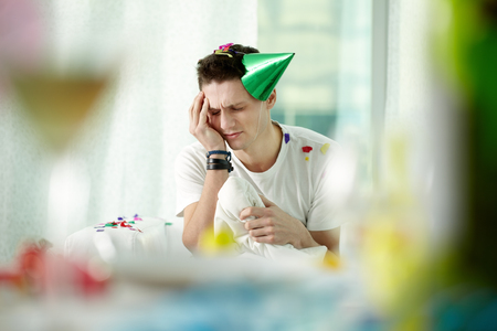 rowdy: Man in party hat suffering from drunken headache after a cheerful party Stock Photo