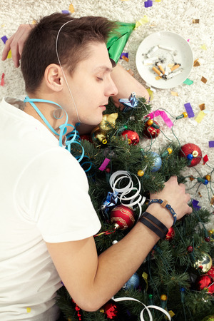 rowdy: Young drunken man sleeping on floor with Christmas tree after the party