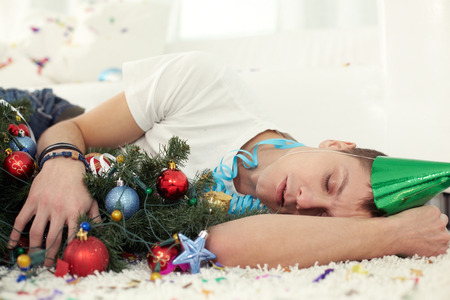 agotado: Young drunken man sleeping on floor with Christmas tree and in party hat