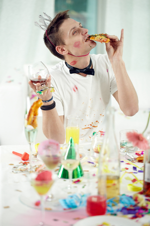 rowdy: Young drunken man eating and drinking up remnants of festive meal after party