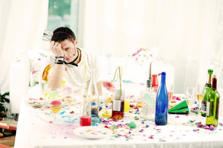 after party: Young man sitting at messy table after turbulent party Stock Photo