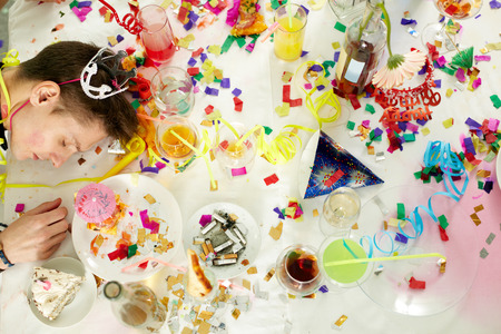 mess: Messy table with confetti and alcohol and drunken man on it