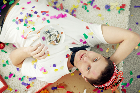 after party: High angle view of a young man lying on back with cigarette butts and looking at camera at his birthday Stock Photo