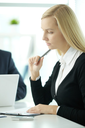 Young business woman thinking over papers in office