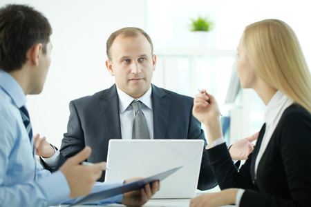 interrogating: Business people submitting proposals at meeting