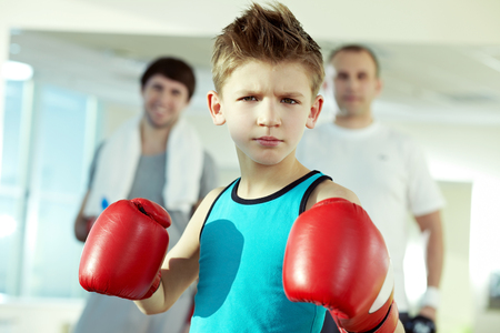 boy boxing: Little serious boys in boxing gloves looking at camera