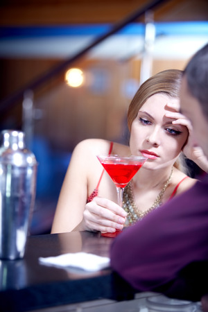 woman bar: Young beautiful girl grieving at bar