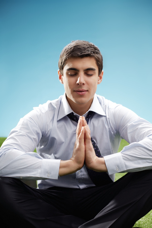 young businessman: Portrait of young meditating businessman Stock Photo