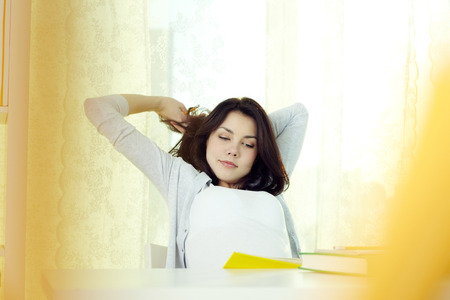 studious: Young student girl stretching herself while doing homework Stock Photo