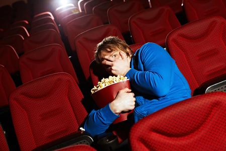 若い男が映画館でホラー映画を見て