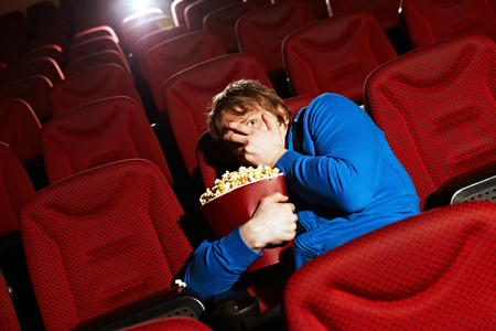Young man watching horror film in cinema hall Imagens
