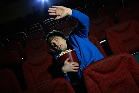 terrified: Young man is terrified by the scene seen on the screen in cinema hall Stock Photo