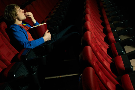 spectator: Row of chairs in cinema hall with man sitting their alone